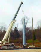 Crane lifting a blue cellphone tower